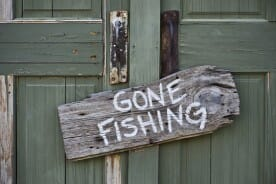 gone fishing sign on an old green door