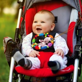 a smiling baby in a baby stroller
